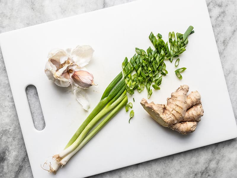 Garlic, sliced green onion, and ginger on a cutting board.