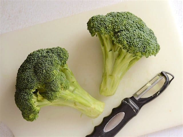 Two crowns of broccoli on a cutting board with a vegetable peeler
