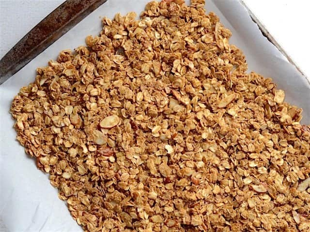 unbaked granola spread on a parchment lined baking sheet