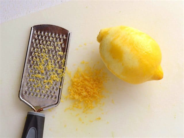 Zested lemon on a cutting board with a zester