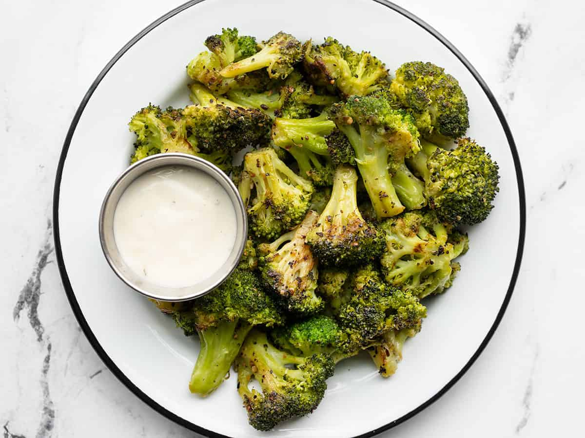 a plate full of oven roasted frozen broccoli and a cup of ranch dressing