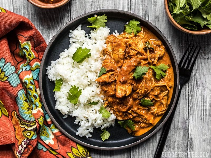 A plate full of slow cooker chicken tikka masala served with rice and cilantro, a colorful napkin on the side.