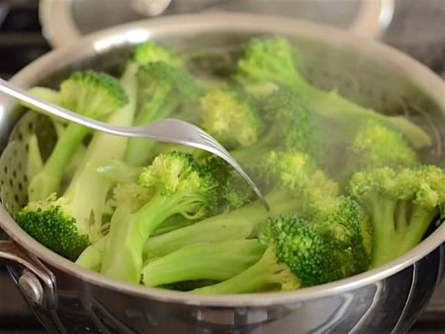 Steamed Broccoli being tested with a fork