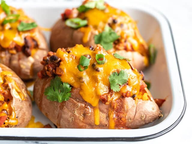 Side view of turkey chili smothered sweet potatoes in a baking dish, topped with green onion and cilantro