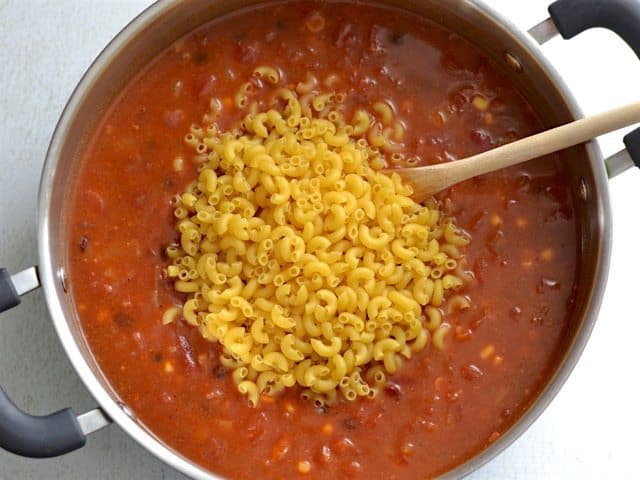 Uncooked macaroni added to the pot