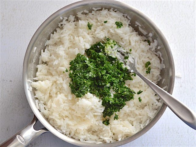Lemon parsley mixture added to cooked rice in a sauce pot