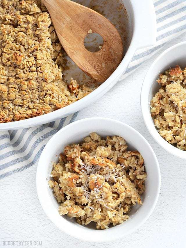 Banana Coconut Baked Oatmeal served into two bowls, casserole dish with a wooden spoon on the side