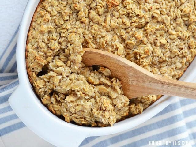 Banana Coconut Baked Oatmeal in a casserole dish being scooped out with a wooden spoon