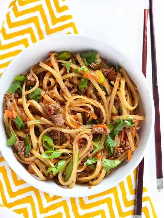 Overhead view of a big bowl of beef stir fry noodles on a yellow and white napkin, chopsticks on the side