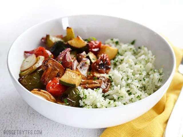 Broiled Balsamic Vegetables served over lemon parsley rice, in a bowl, sitting on a yellow napkin. Side view.