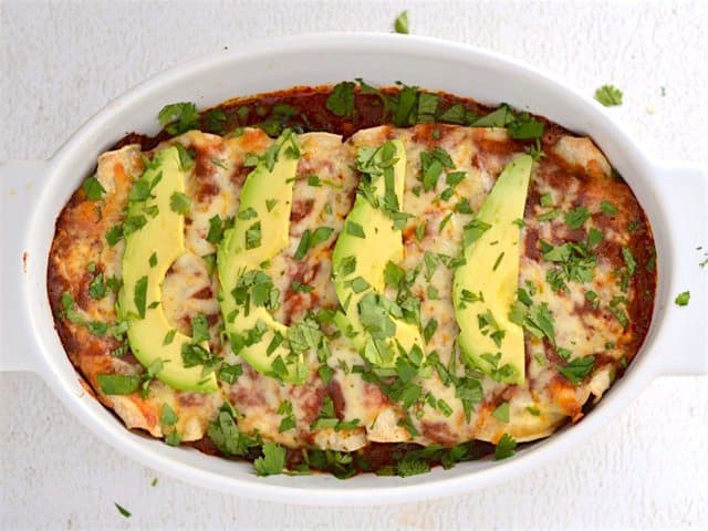 Finished Weeknight Enchiladas, topped with avocado and cilantro