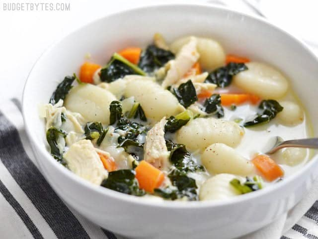 Side view of a bowl of creamy chicken gnocchi soup with kale, a spoon in the center