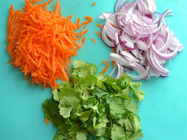 Shredded carrots, sliced red onions, and cilantro on a cutting board