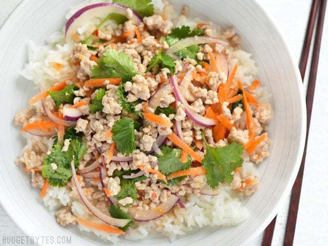 Finished Nam Sod (Thai Pork Salad) in a bowl with rice and chopsticks on the side