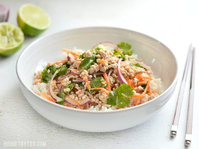 Side view of a bowl full of nam sod (Thai Pork Salad), with limes in the background and chopsticks on the side