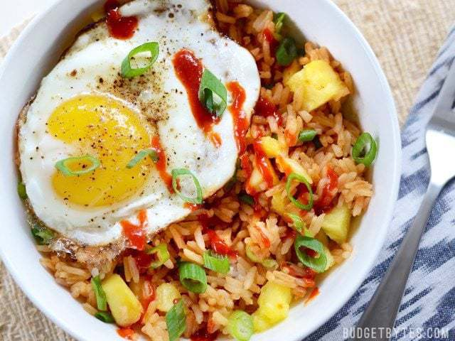 Close up overhead view of a pineapple sriracha breakfast bowl with a fried egg on top