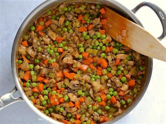 Lentils and peas added to vegetables and gravy in the skillet