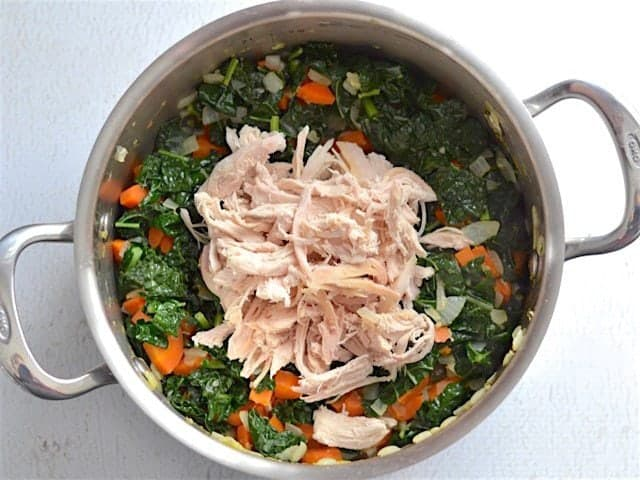 Wilted Kale and Shredded Chicken added to the soup pot