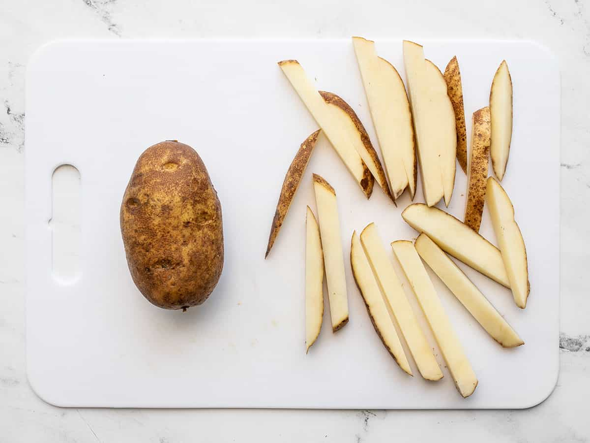 Two russet potatoes on a cutting board, one cut into fries