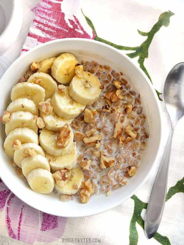 A bowl of Banana Nut Breakfast Farro with sliced banana on top, the bowl on a floral cloth napkin