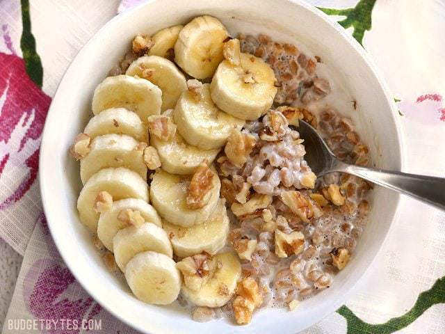A bowl of Banana Nut Breakfast Farro topped with sliced bananas and walnuts, a spoon in the center