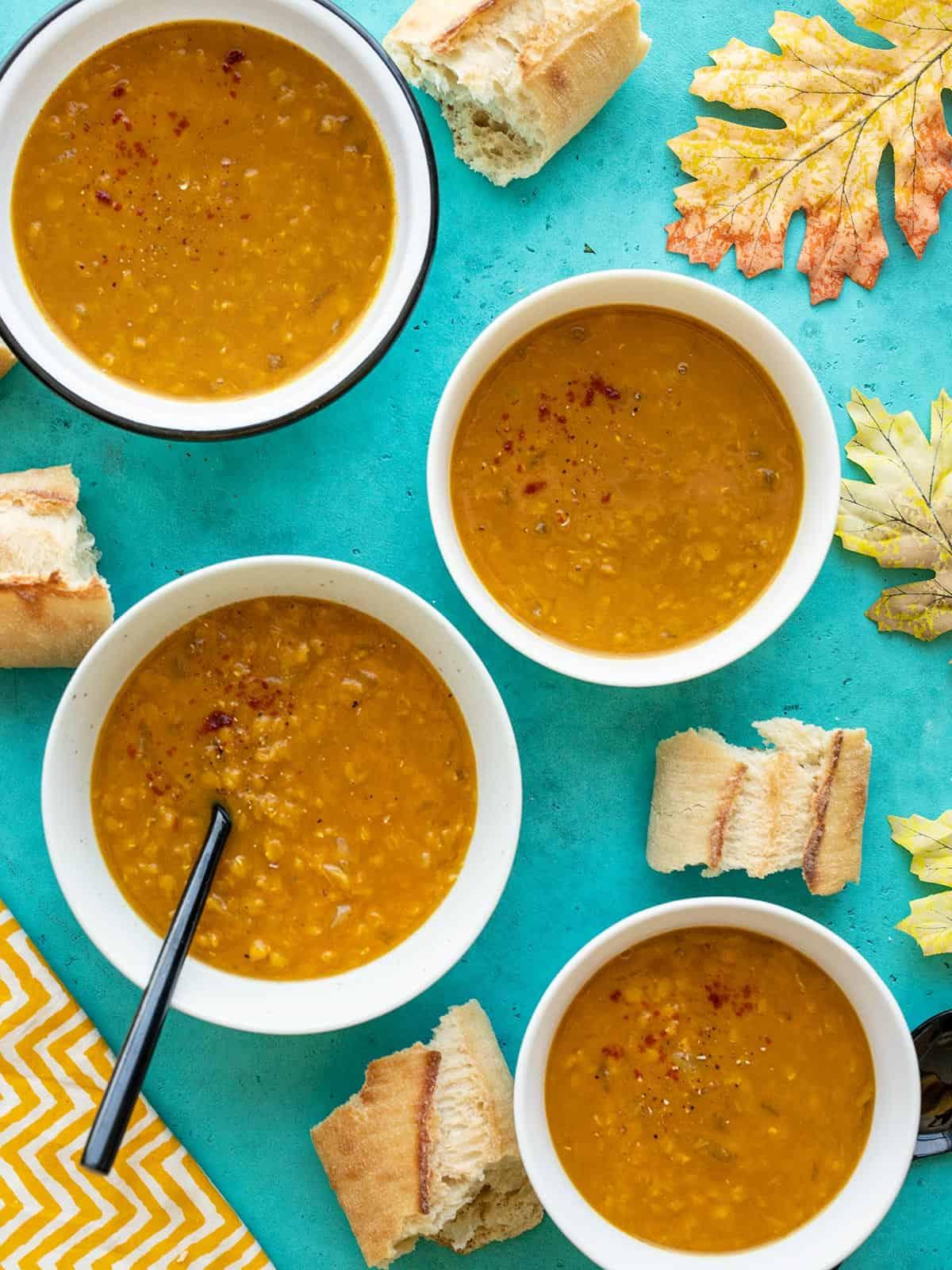 Four bowls of curried red lentil and pumpkin soup with bread and leaves scattered around the bowls