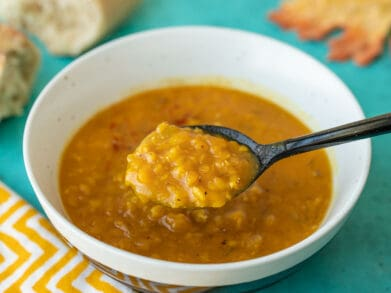 A spoonful of lentil and pumpkin soup being lifted from the bowl