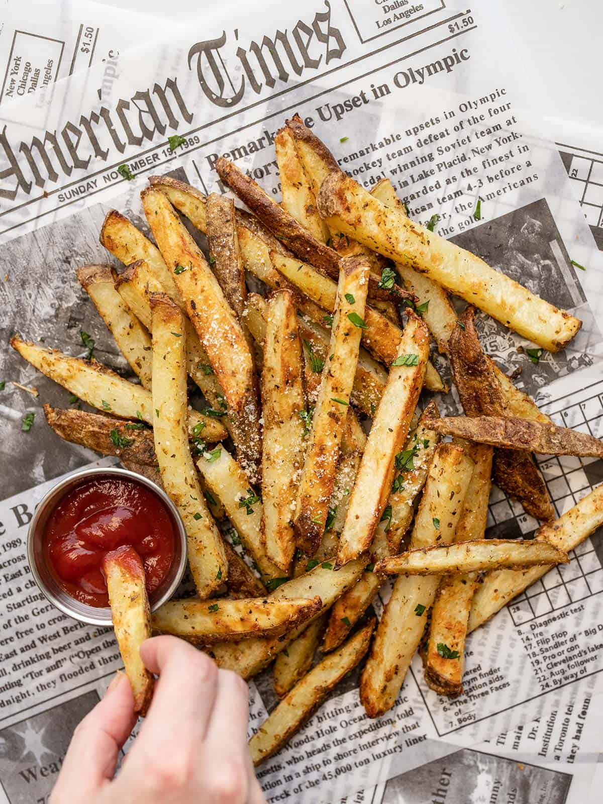 a hand dipping one garlic parmesan fry into ketchup next to a pile of fries