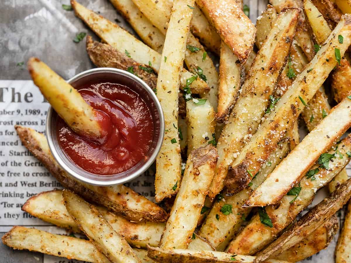 close up view of garlic parmesan fries and a cup of ketcheup