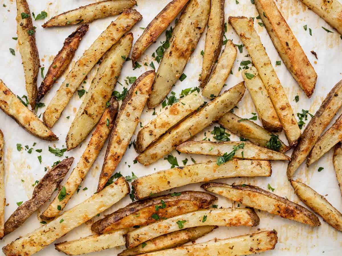 baked garlic parmesan fries on a baking sheet garnished with parsley
