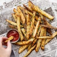 a hand dipping a fry into a cup of ketchup next to a pile of fries