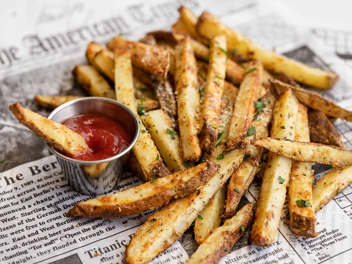 Side view of a pile of Garlic Parmesan fries with a small cup of ketchup