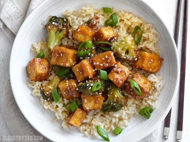 Finished pan fried sesame tofu with broccoli and brown rice in a white bowl