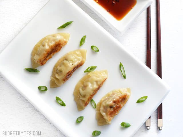 Four Pork Gyoza on a plate, sprinkled with green onion, next to a dish of soy sauce.