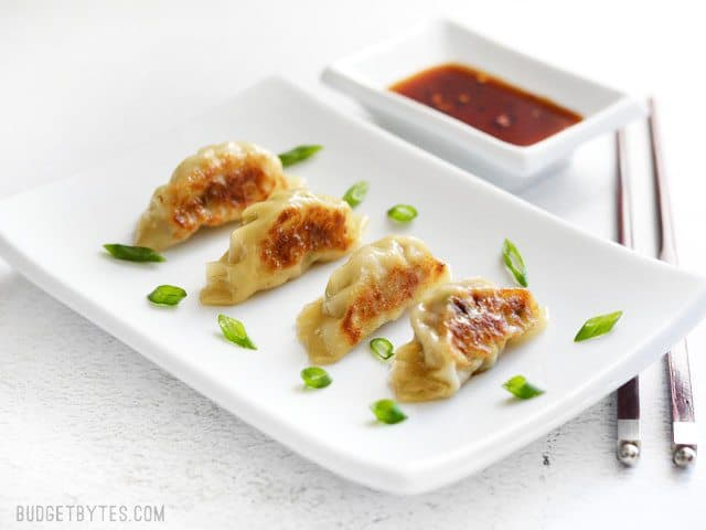 four Pork Gyoza on a rectangular white ceramic plate next to a small dish of soy sauce.