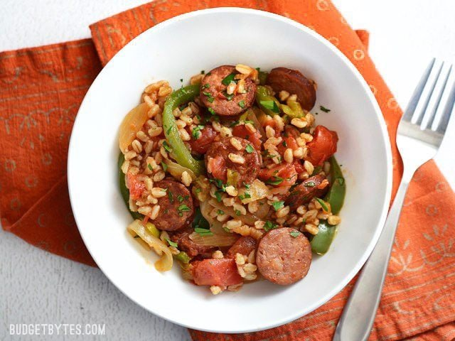 Smoked sausage and peppers with farro served in a bowl, on an orange napkin, fork on the side