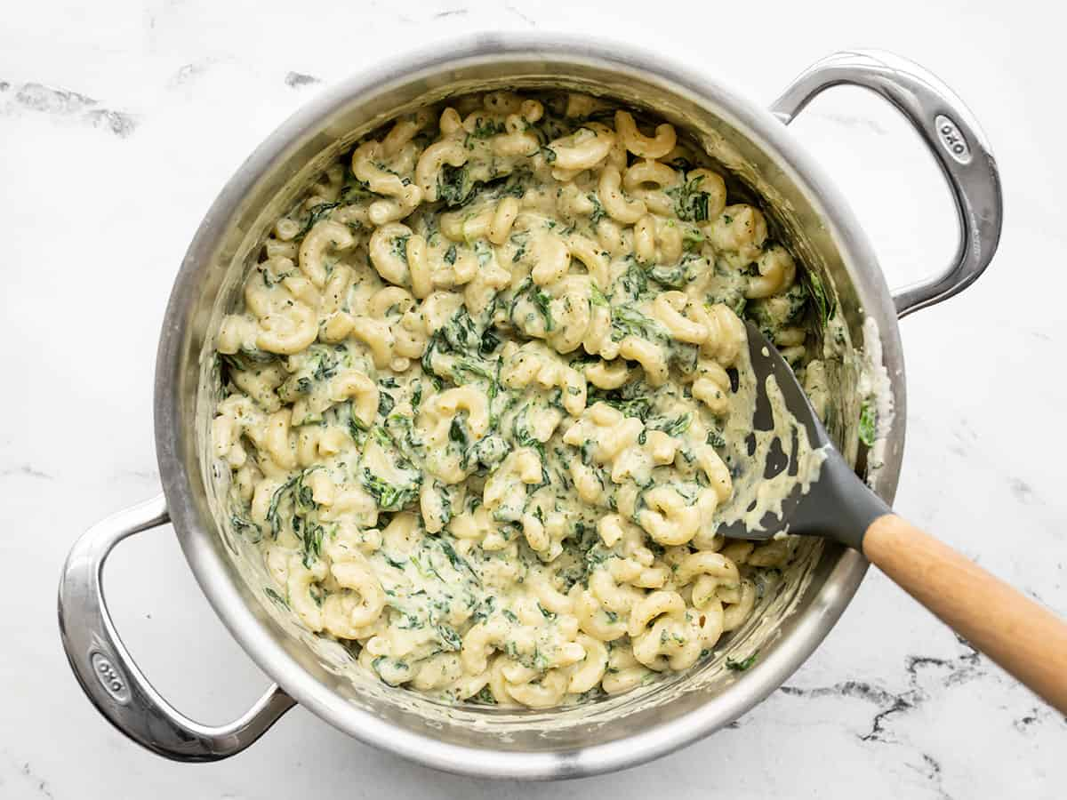 Finished creamy pesto mac in a pot with a large spoon
