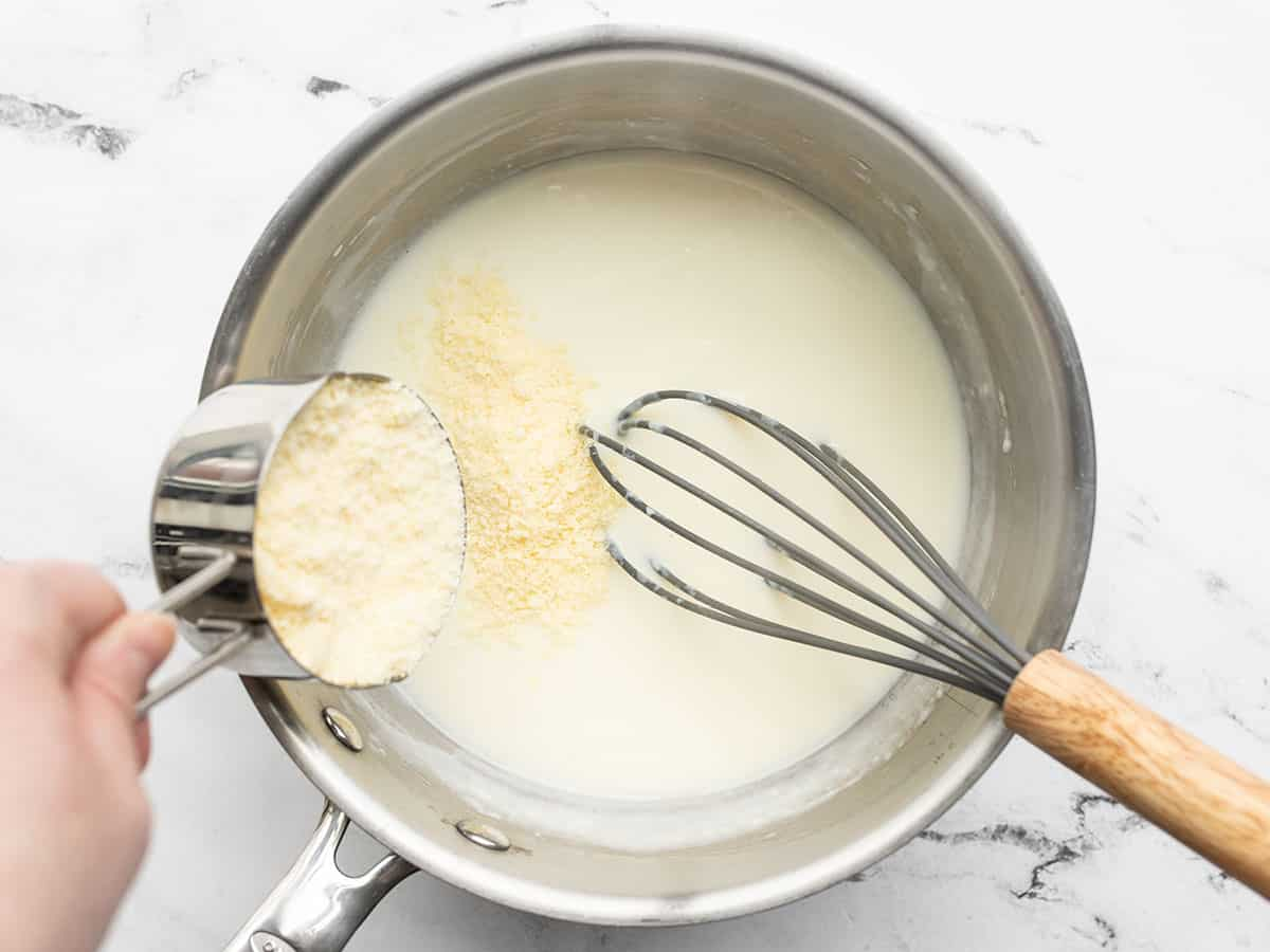 Grated Parmesan being added to the sauce pot