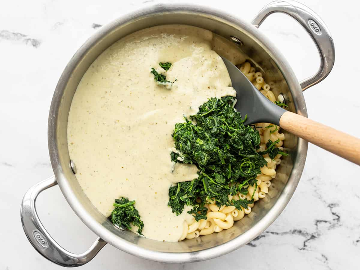Creamy pesto sauce and spinach added to the pot with the cooked macaroni