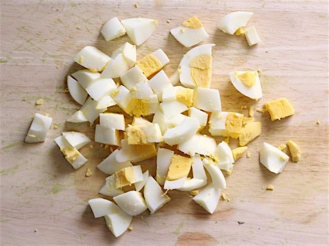Diced hard boiled eggs on a wooden cutting board