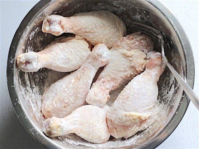 Raw chicken drumsticks coated in cornstarch