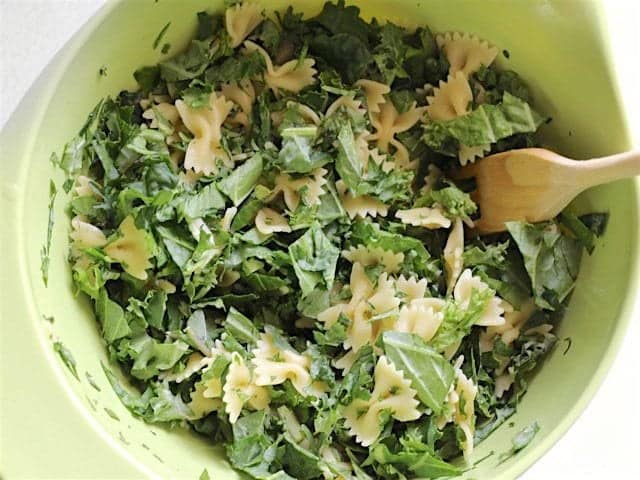 Pasta and Kale in a large bowl with a wooden pasta fork