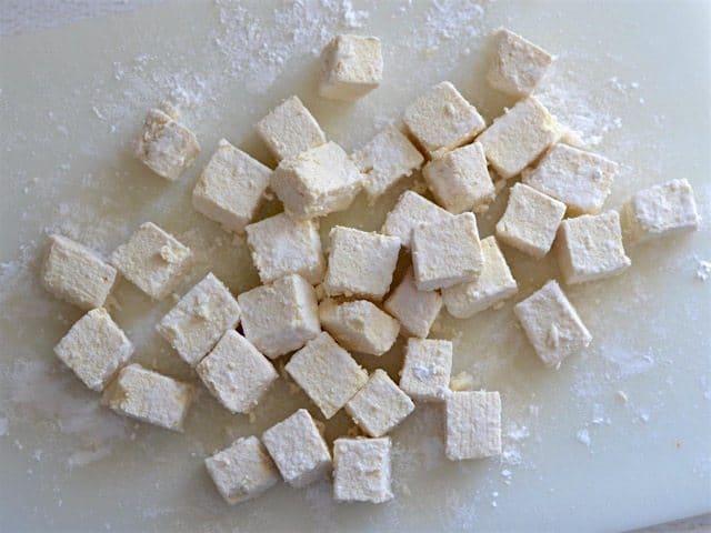 Cubed tofu coated in cornstarch on a cutting board
