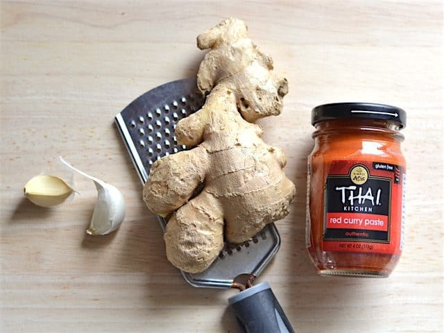 Garlic, Ginger sitting on a small-holed cheese grater, and a jar of Thai Curry Paste on a wooden cutting board