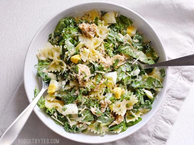 Kale and salmon caesar salad tossed and coated in dressing, in a bowl with two forks