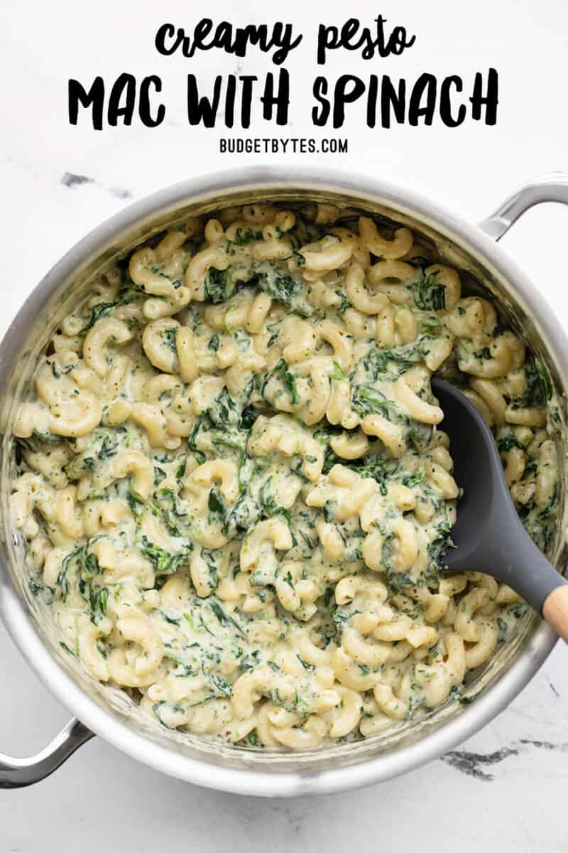Overhead view of a pot full of creamy pesto mac with spinach, title text at the top
