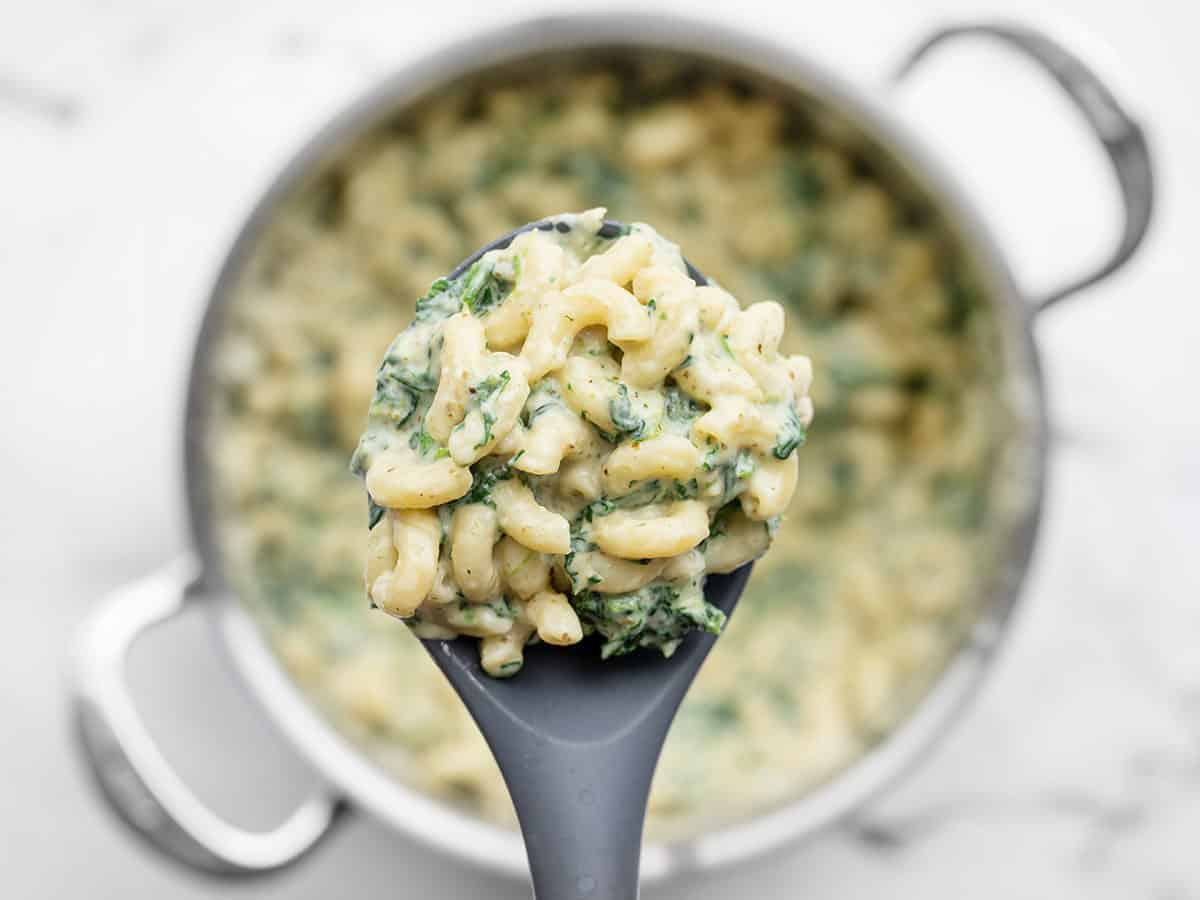 Close up of a spoonful of creamy pesto mac with the pot in the background