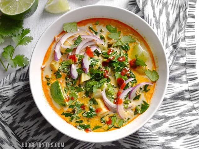 Thai Curry Vegetable Soup fully garnished with lime wedges, thinly sliced red onion, cilantro, and sriracha.