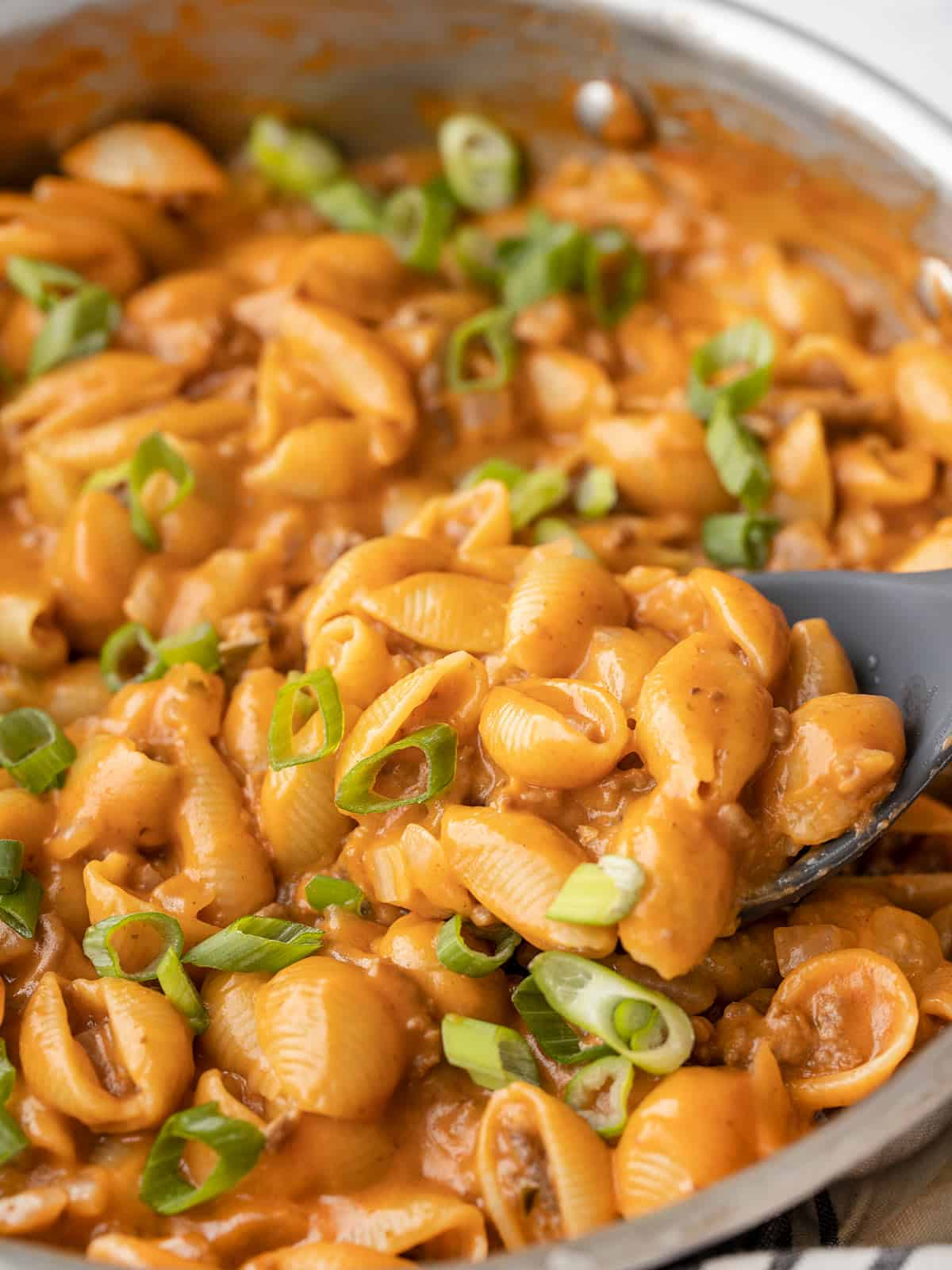 Close up side view of cheeseburger pasta skillet with a spoon dug in the side