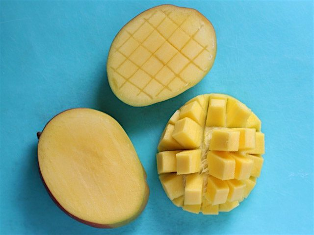 Cubed Mangoes on a blue cutting board